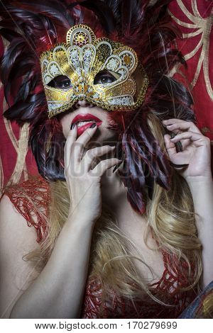 Mysterious, Beautiful blond woman with mysterious mask with red feathers. The background has floral motifs in garnet and gold