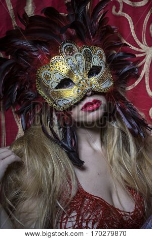 Golden, Beautiful blond woman with mysterious mask with red feathers. The background has floral motifs in garnet and gold