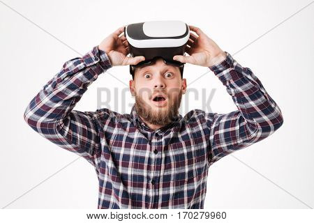 Surprised Bearded man in shirt takes off virtual reality device with open mouth and looking at camera. Isolated white background