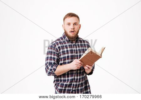 Surprised Bearded man in shirt holding book in hands in studio and looking at camera. Isolated white background