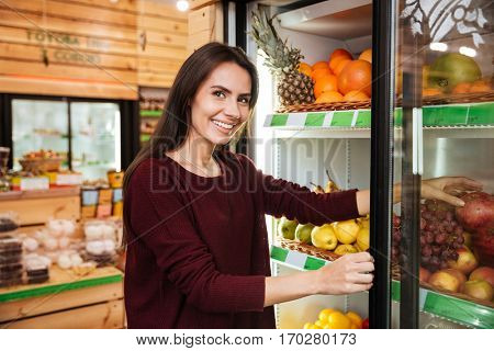 Happy beautiful young woman standing and choosing fruits in grocery store
