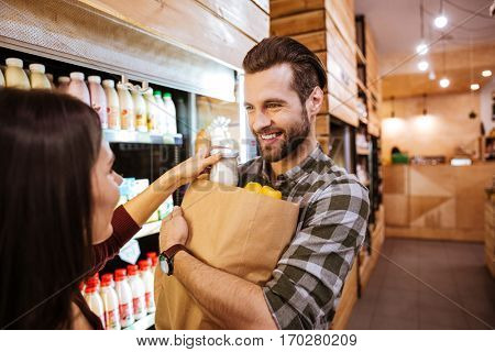 Happy young couple with packet of food in grocery shop