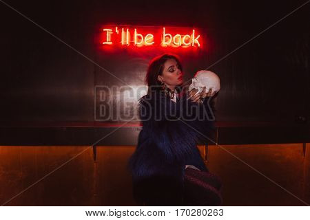 Sensual young woman in fur coat holding and looking at skull sitting over background with glowing inscription I'll be back