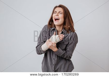 Image of sick screaming young lady with the plaster on hand dressed in shirt standing isolated over gray background.