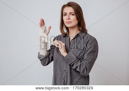 Picture of sick young lady with the plaster on hand dressed in shirt standing isolated over gray background.