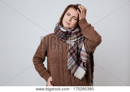 Sick young woman in sweater and scarf with closed eyes touching her head. Isolated gray background