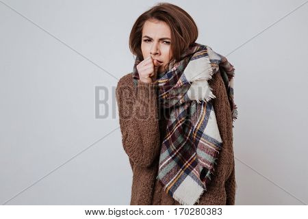 Freeze woman in sweater and scarf holding hand near the mouth and looking at camera. Isolated gray background