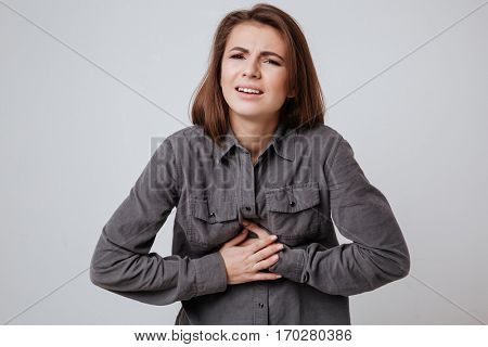 Image of sick young lady dressed in shirt standing isolated over gray background and touching belly.