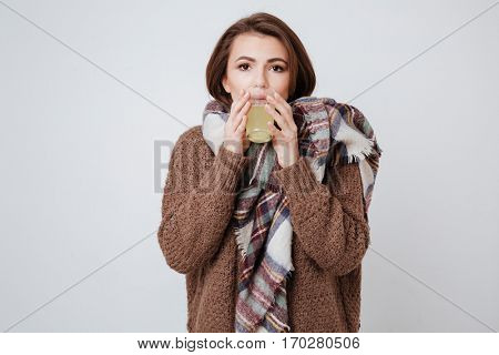 Sick young lady in sweater and scarf holding glass with medicine and looking at camera. Isolated gray background