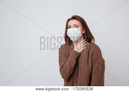 Woman in sweater and medical mask holding her neck and looking at camera. Isolated gray background