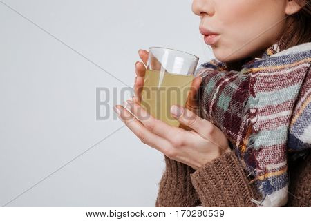 Cropped photo of sick young woman in sweater and scarf holding glass with medicine and drinking. Isolated over gray background.