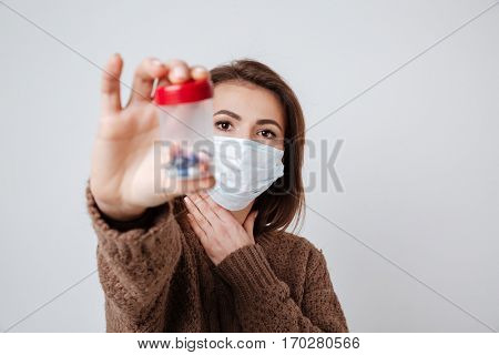 Woman in sweater and medical mask holding medical tablets and showing theirs at camera. Isolated gray background