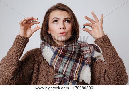 Picture of attractive sick young lady in sweater and scarf choosing medicine pills. Isolated over gray background.