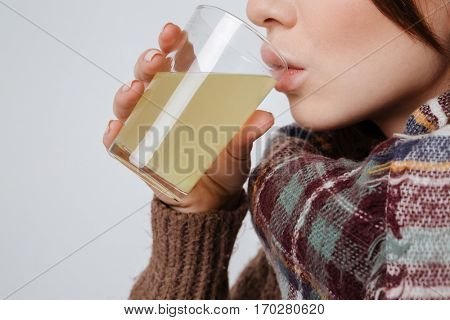 Cropped image of sick young lady in sweater and scarf holding glass with medicine and drinking. Isolated over gray background.