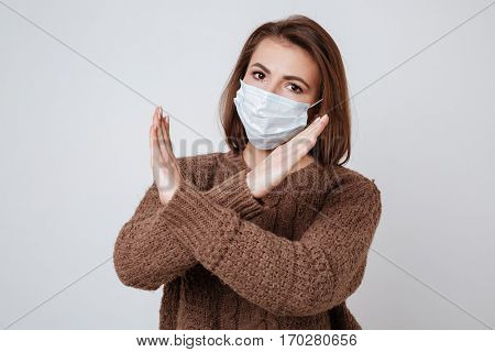 Sick Woman in sweater and medical mask showing stop gesture and looking at camera. Isolated gray background