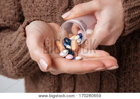 Cropped image of woman in sweater preparing uses medical tablet. Isolated gray background