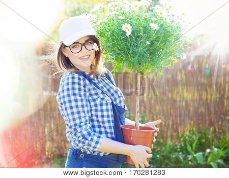 Young woman holding a flower pot standing in the garden, spring gardening concept