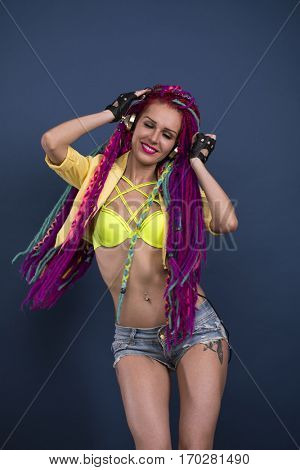 Stylish woman listening to music on headphones. Sexual girl with fascinating dreadlocks posing in studio. Acid style