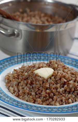 Buckwheat cereal with butter on the plate and in the pan