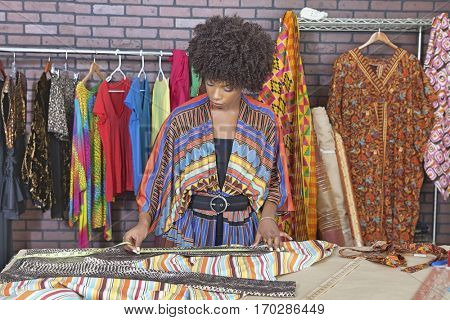African American female designer measuring cloth at design studio