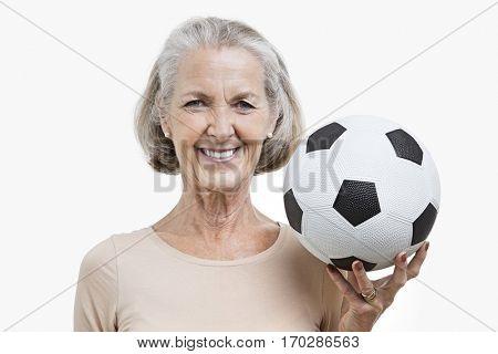 Portrait of senior woman holding soccer ball against white background