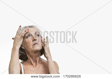 Senior woman suffering from headache against white background