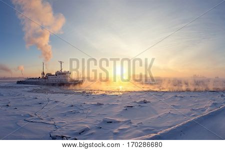 Ice Breaker Breaks Ice on Frozen River at Sunset. Panoramic View.