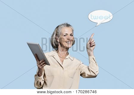 Portrait of senior woman with tablet PC pointing at tweet bubble against blue background