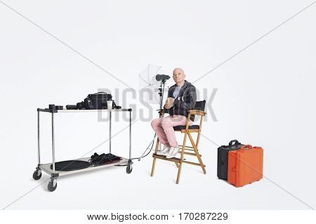 Photographer sitting on director's chair with equipments in studio