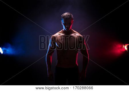 Awesome bodybuilder silhouette. Handsome power athletic man bodybuilder. Fitness muscular body on dark colour smoke background. Perfect male. tattoo, posing.