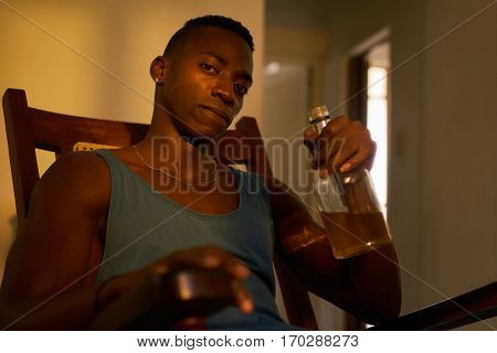 Social issues substance abuse with alcoholic young black man drinking alchool from liquor bottle at home looking at camera holding bottle of whiskey.