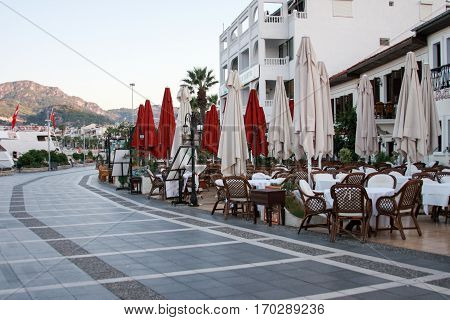 MARMARIS TURKEY - SEPTEMBER 11: Outdoor cafe and restaurant on sea-front street of Marmaris with mountains on background