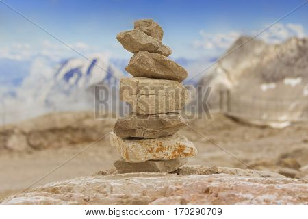 Stone tower in mountains height show balance stability power. Stones stack in mountain panorama with blue sky visualizes creativity consulting success or showing health meditation and therapy.