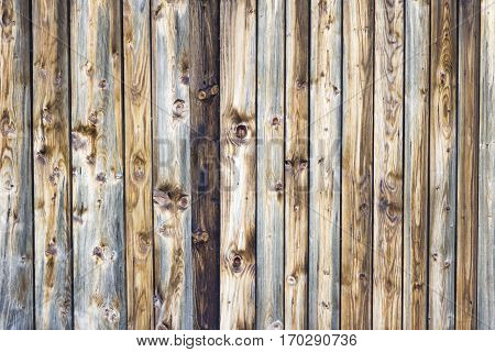Wooden texture background in vertical brown laths and knotholes. The pattern consists of wood aged by weather. The handmade construction has warm colors and is best for parquet floors or a wall.