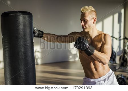 Shirtless handsome muscular young man in gym giving punch to punching bag, wearing boxing gloves