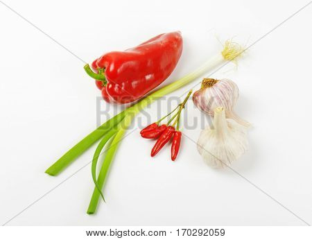 Red sweet pepper, chili peppers, scallion and garlic on white background