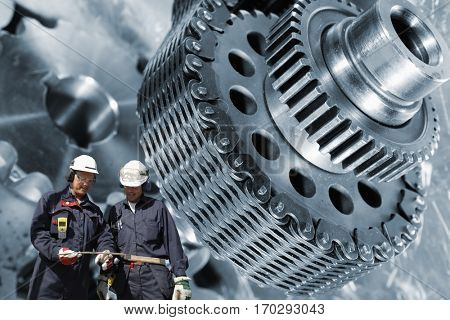 two industry workers and large gears machinery, slight metal blue toning