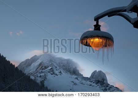 Snow and icicle covered amber light post against backdrop of the wind sweeping across the mountain ridge of Aiguille Verte and Les Drus