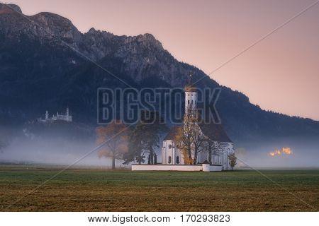 Saint Coloman church with warm light shining through the fog during amazing sunrise near Neuschwanstein Castle Fussen Bavaria Germany