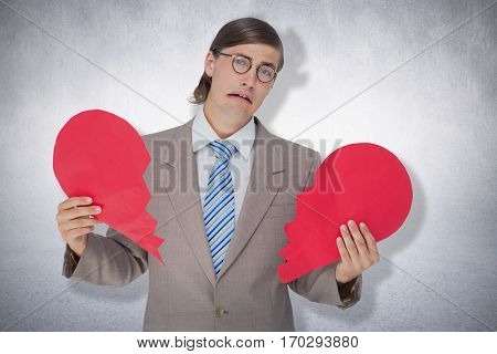 Geeky businessman crying and holding broken heart card against white wall