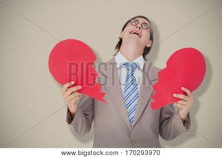 Geeky businessman crying and holding broken heart card against cream