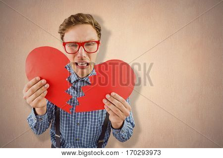 Geeky hipster holding a broken heart against a beige wall