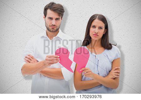 Upset couple holding two halves of broken heart against grey