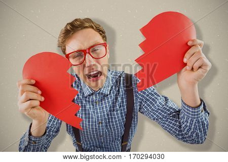 Geeky hipster holding a broken heart against grey