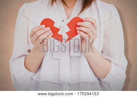 Woman holding broken heart paper against a beige wall