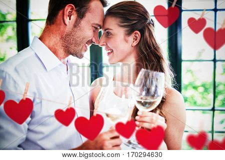 Hearts hanging on a line against couple looking face to face and toasting wine glasses