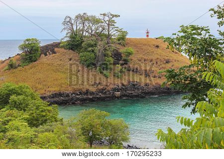 Lagoa Azul ( Blue Lake) a beautiful beach with baobab and a lighthouse up the cliff in Sao Tome and Principe Island, in Africa
