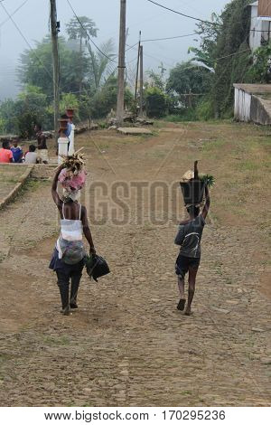 Sao Tome, Sao Tome and Principe - July 22, 2015: Unidentified people carrying firewood and fruits in a village