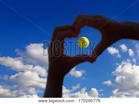 view of tennis ball midair with cloudy sky above