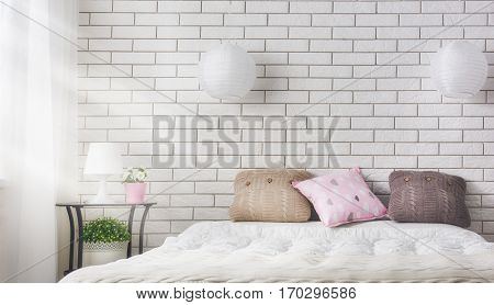 Bedroom in soft light colors. Big comfortable double bed in elegant classic room.